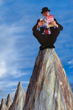 Businessman Reading Magazine on Pinnacle